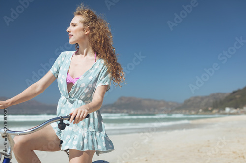 Happy woman riding bicycle at beach on a sunny day