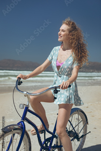 Happy woman riding bicycle at beach