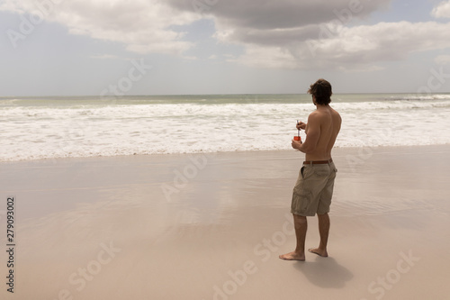 Young man with drink standing on beach