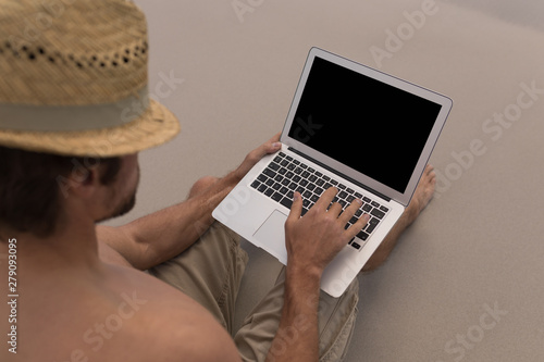 Shirtless young man with hat using laptop on the beach