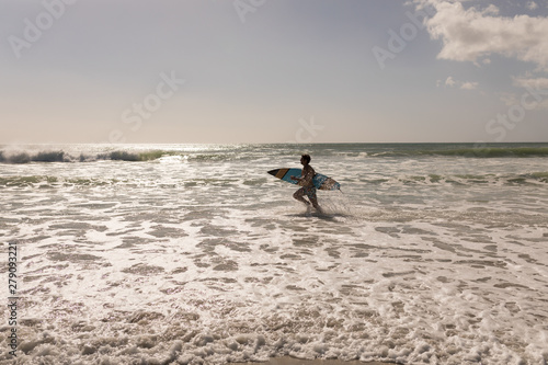 Young male surfer with surfboard running on beach