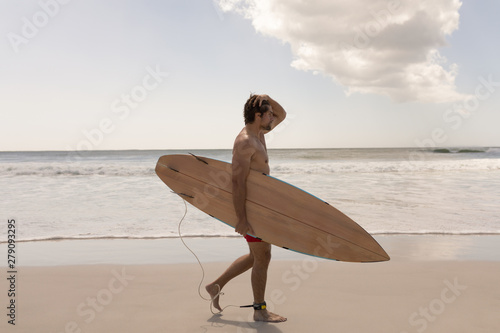 Young male surfer with surfboard standing on beach