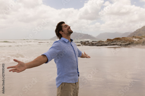 Man standing with arms outstretched on the beach