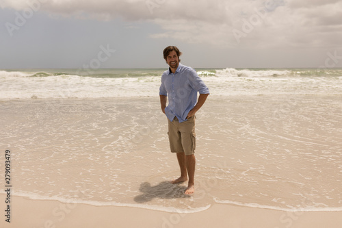Man standing with hands on hip on the beach