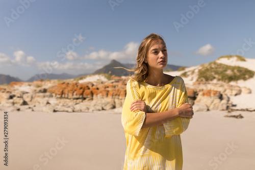 Thoughtful young woman walking on beach