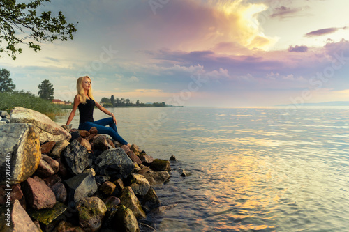Beautiful young woman sits on the rocks by the Balaton lake Wallpaper Mural