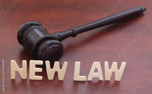 Fotomural  New laws concept. Words NEW LAW and judge gavel on table.