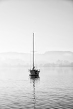 Stunning Unplugged Fine Art Landscape Image Of Sailing Yacht Sitting Still In Calm Lake Water In Lake District During Peaceful Misty Autumn Fall Sunrise