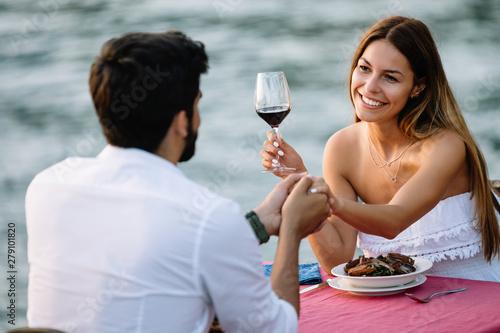 Carta da parati Couple sharing romantic sunset dinner on the beach