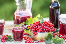 A Selection Of Redcurrant Products - Marmalade Jam Syrup Must And Red Vine On Table In Garden