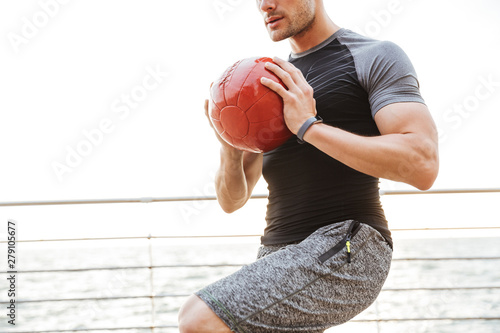 Poster Ouest sauvage Strong young sports man outdoors make exercises with ball.