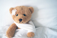 Teddy Bear Lying Sick In Bed With A Headband And A Cloth Covered