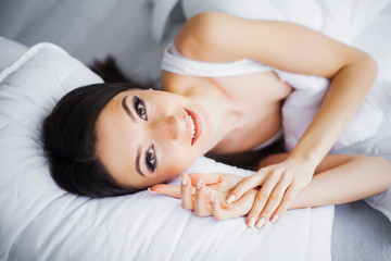 Obraz na płótnie Canvas Young Beautiful Woman Lying on White Bed