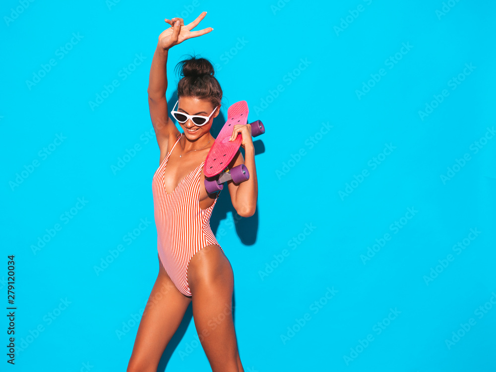 Fototapety, obrazy: Young beautiful sexy smiling hipster woman in sunglasses.Trendy girl in summer swimwear bathing suit. Positive female going crazy with pink penny skateboard,isolated on blue.