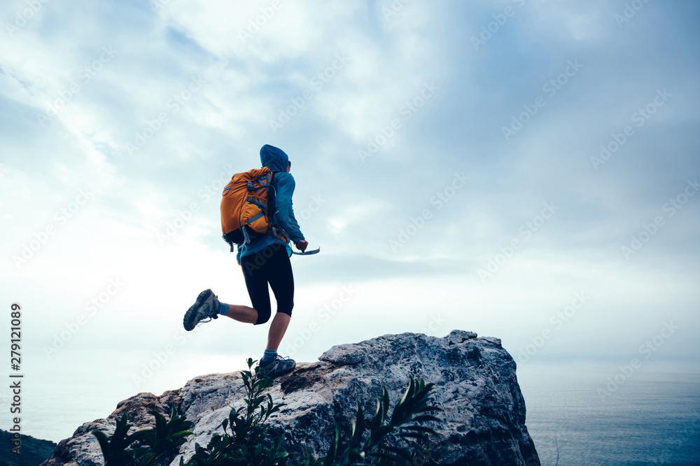Fototapety, obrazy: Successful woman hiker running to on seaside mountain peak cliff edge