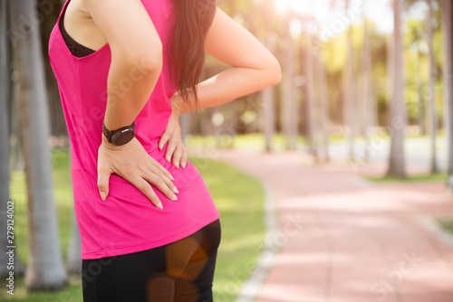Fotomural  Young asian woman feel pain on her back and hip while exercising, healthcare concept