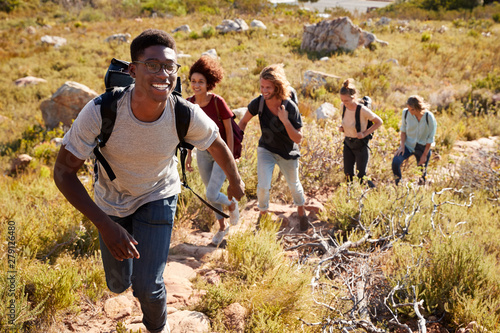 Obraz Millennial African American man leading friends hiking single file uphill on a path in countryside - fototapety do salonu
