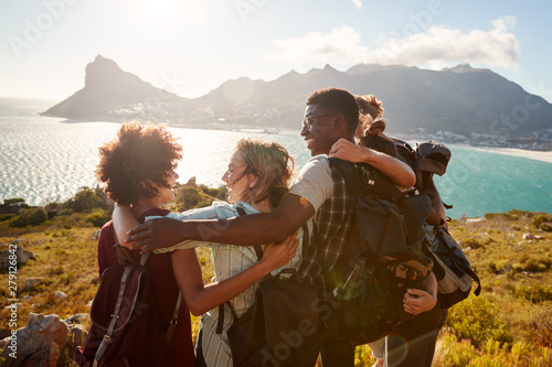 Fotografía  Millennial friends on a hiking trip embrace at the summit to celebrate their cli