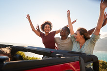 Excited Millennial Friends Travelling In The Back Of An Open Car With Their Arms In The Air