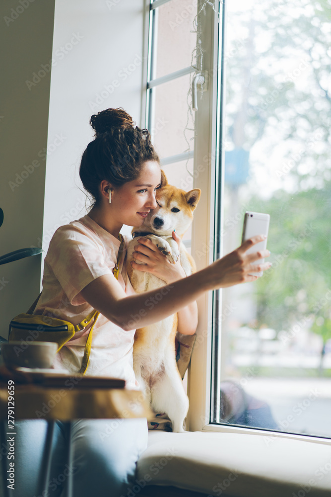 Fototapety, obrazy: Cute woman taking selfie with shiba inu dog sitting on window sill in cafe using smartphone camera holding device posing smiling. People and animals concept.