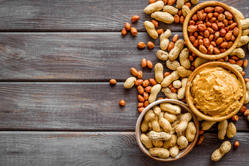 Make peanut butter with paste in glass bowl on wooden background top view copyspace