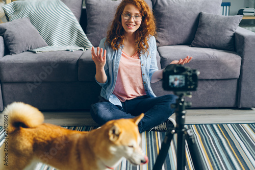 Fotografija  Cute teenager popular blogger is recording videoblog sitting on floor at home, stroking lovely pet dog and talking to subscribers