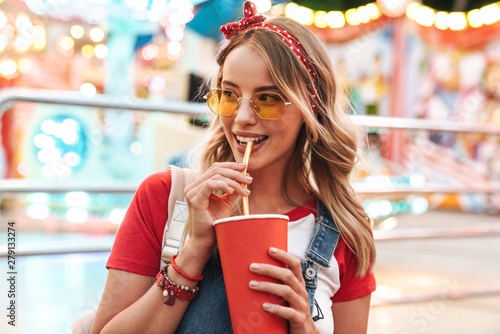Image of attractive charming woman drinking soda beverage from paper cup while w Fototapet