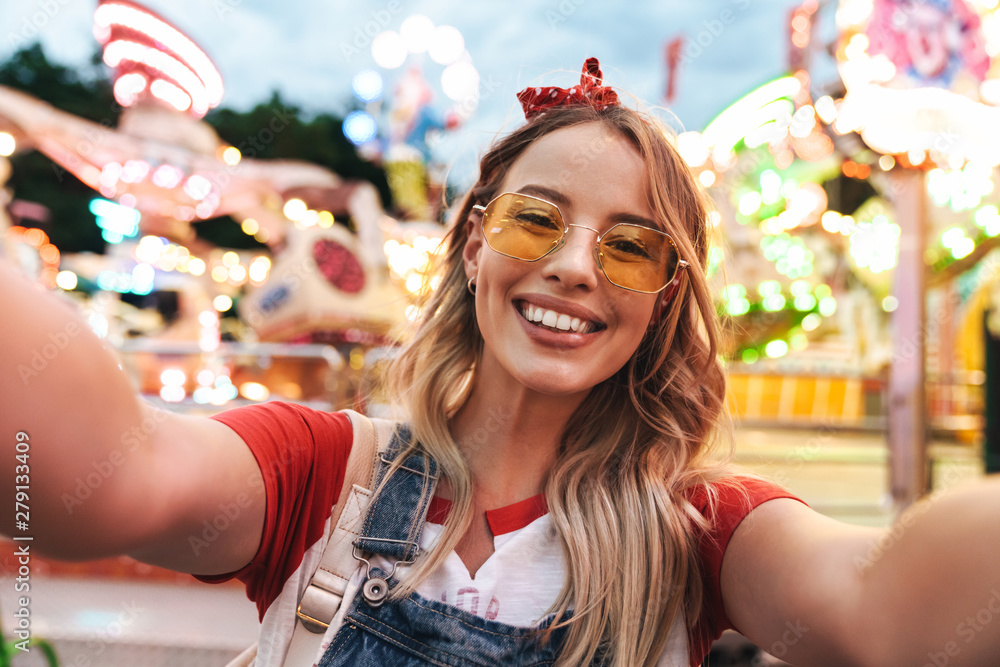 Fototapety, obrazy: Image of young blonde woman laughing and taking selfie photo at amusement park