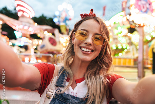 La pose en embrasure Attraction parc Image of young blonde woman laughing and taking selfie photo at amusement park