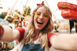 Image of cheerful blonde woman laughing and taking selfie photo at amusement park