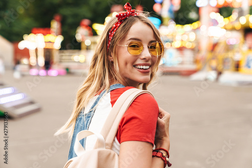 Fotobehang Amusementspark Image of pleased blonde woman smiling and walking in front of colorful carousel at amusement park