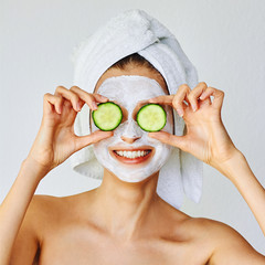 Beautiful young woman with facial mask on her face holding slices of cucumber...