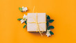 canvas print picture Floral art and craft. Orange background with beige paper gift box and mistletoe arrangement. Copy space.