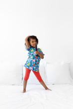 Young Girl Standing On Bed Singing With Hairbrush As A Microphone