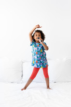 Young Child Singing With Hairbrush As A Microphone Dancing On Bed
