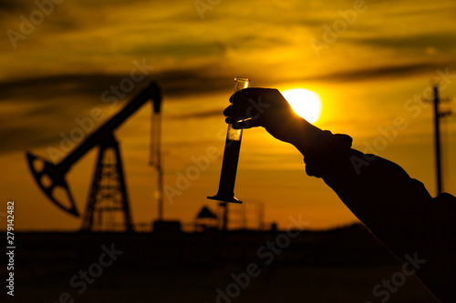 A man holding a flask of oil. Oil rigs in the background. Oil production in Russia. Sunset.