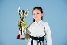 Winner Little Girl In Gi Sportswear. Practicing Kung Fu. Happy Childhood. Sport Success In Single Combat. Girl With Champion Cup. Martial Arts. Knockout. Energy And Activity. Everything Is Possible