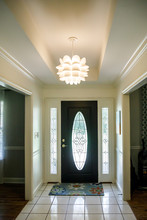 Front Entrance Of A Traditional Home With A Modern Lighting Fixture And Tray Ceiling