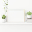 Interior poster mockup with horizontal gold metal frame standing on the table with plants in pots and pile of books on empty white wall background. 3D rendering, illustration.