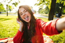 Image Of Funny Girl With Tongue Sticking Out Using Headphones And Taking Selfie Photo While Sitting In Green Park