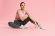 Fitness woman model in fashion sportswear on pink background