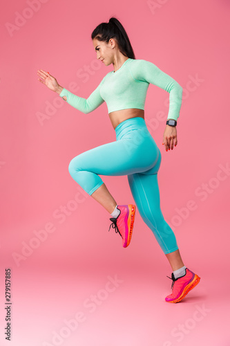 Obraz Serious young sports fitness woman isolated over pink wall background running. - fototapety do salonu