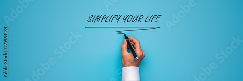 Fotografie, Obraz  Male hand writing a Simplify your life sign with black marker over