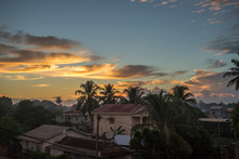 Beautiful Golden Light In Clouds Above The Jungle Town Of Manakara, Madagascar.  Houses With Phonelines And Satellite Dishes Standing Between Palm Trees After Sunset.