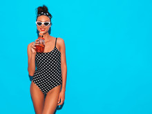 Young Beautiful Sexy Smiling Hipster Woman In Sunglasses.Girl In Summer Peas Swimwear Bathing Suit.Posing Near Blue Wall,drinking Fresh Cocktail Smoozy Drink