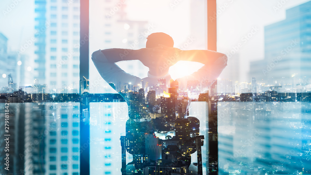 Fototapeta Portrait of relaxed businessman in modern office.Double exposure city of Business young man relax after work of office window with business district view.