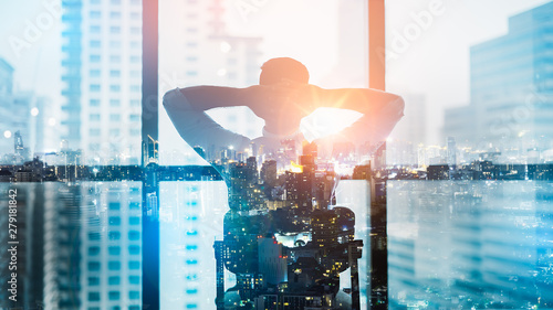 Obraz Portrait of relaxed businessman in modern office.Double exposure city of Business young man relax after work of office window with business district view. - fototapety do salonu