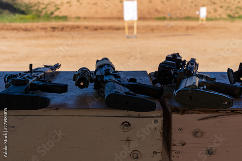 Fotomural Semi-Automatic Rifles laying on bench at outdoor firearms shooting range