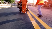 Selective Focus Of Road Workers With Thermoplastic Spray Road Marking Machine Working To Paint Yellow Line On Asphalt Road Surface With Flare Light In Evening Time, Construction Concept
