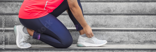 Fotografia  Woman tying shoelace on running shoes before practice